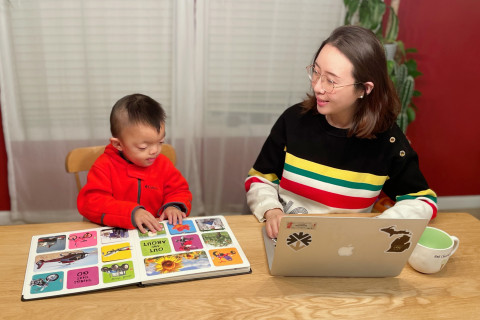 Lingxiao Sun works at home next to her son