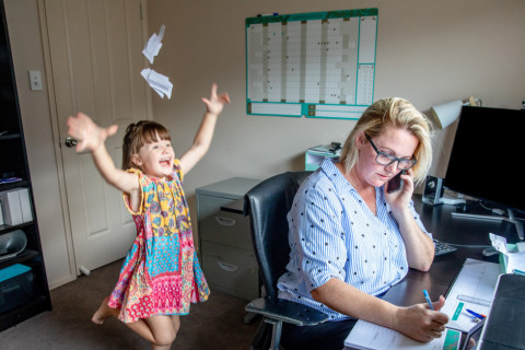 Mother works at computer, on the phone, with child in background playing