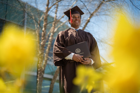 Graduating student standing outside in cap and gown, holding diploma