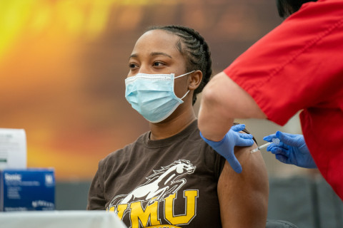 A student wearing a mask getting her COVID-19 vaccination.