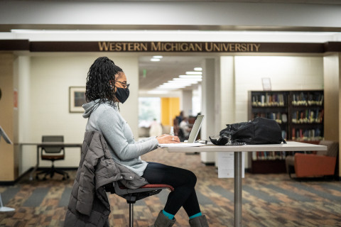 A student wearing a mask studying in the library.