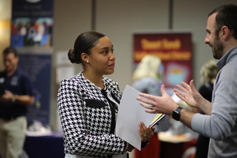 woman speaking with man at job career fair