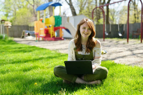 Young woman sitting on the grass smiling in front of a playground: https://wmich.edu/firstyearfaces/kirstin-laduke