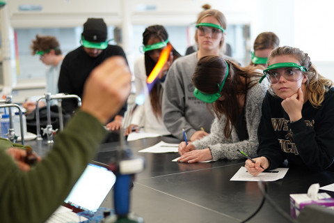 Students in lab observing professor using fire torch