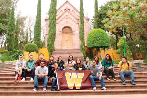 Students sitting on stairs outside of a building holding a Western flag