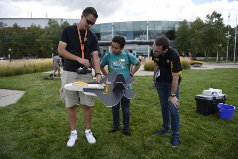 three individuals looking at a drone aircraft
