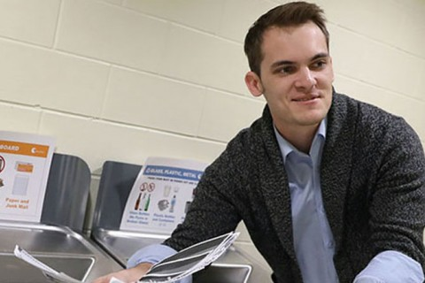 WMU student Joshua Turske placing paper into a recycling bin