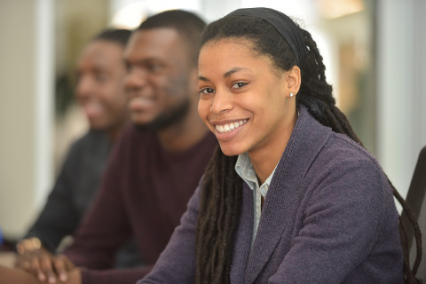 Academic Programs:  This images shows three African American students sitting in a row of chairs. The young woman in the front is in sharp focus and is smiling at the camera, the two men behind are in soft focus.