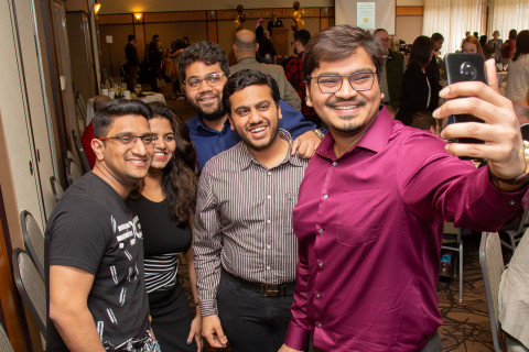 This images shows a diverse group of five students at an event for graduate students. One student is holding a cell phone and taking a selfie with the other four crowded around behind him.  In the background, the room is full of people interacting and mingling with each other.