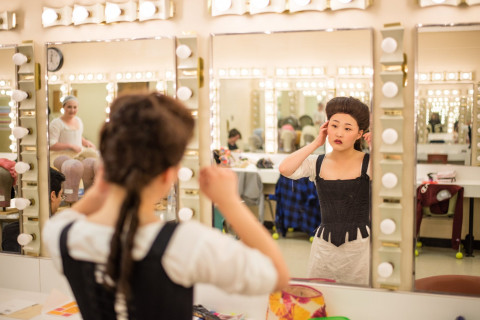 woman in period costume looking in dressing room mirror.