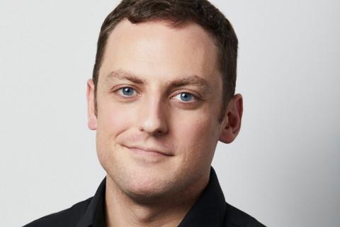 young white man wearing black shirt in portrait setting.