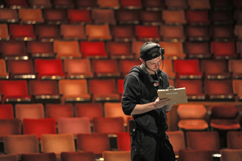 Young man wearing a headset and holding a clipboard standing a theatre.