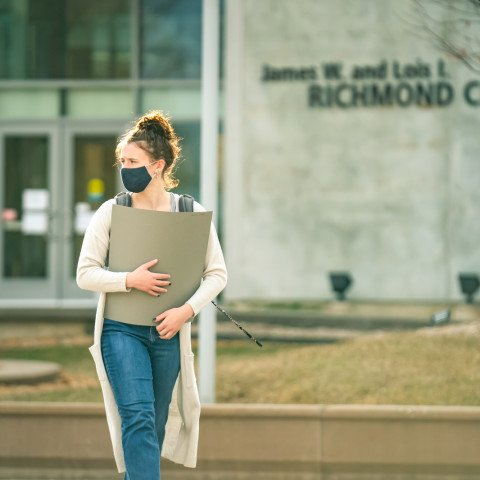 Student holding a portfolio in front of the Richmond Center.