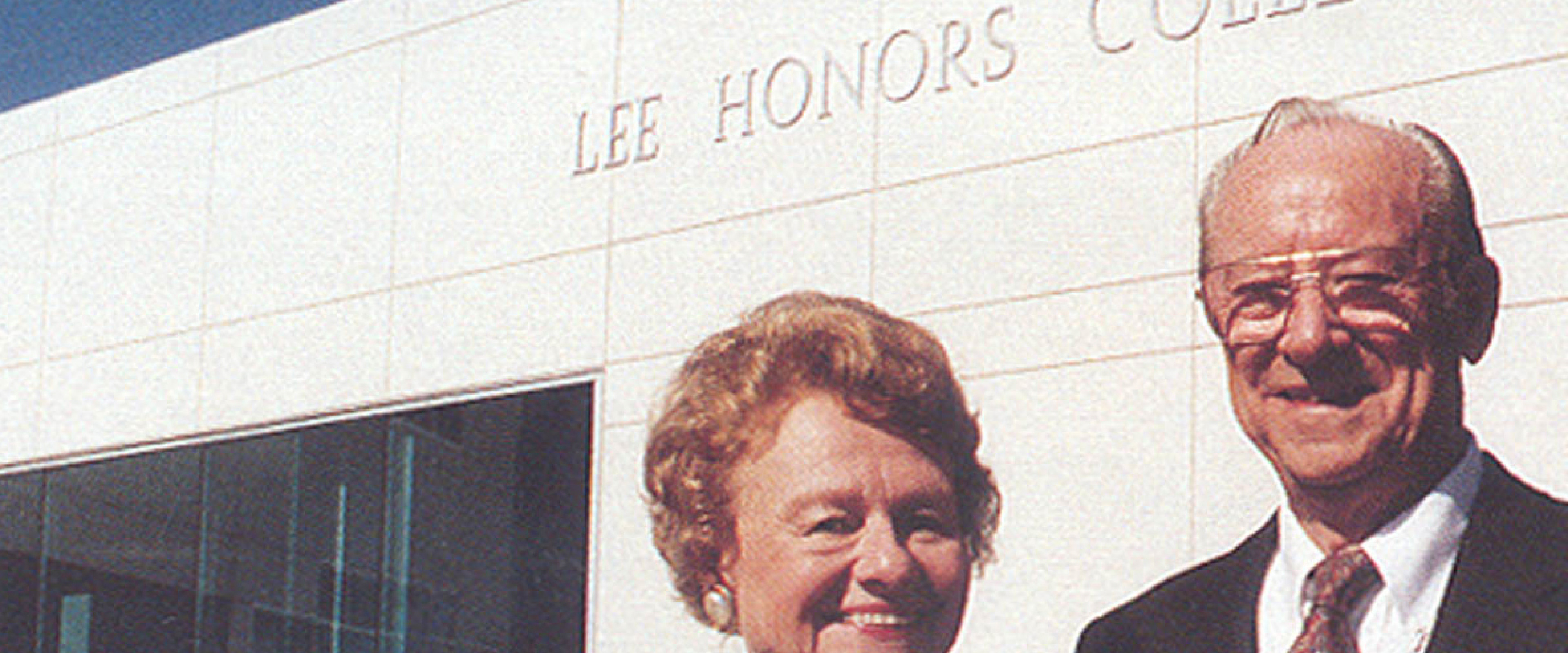 Head and shoulders of Carl and Winifred Lee standing in front of the Lee Honors College building.