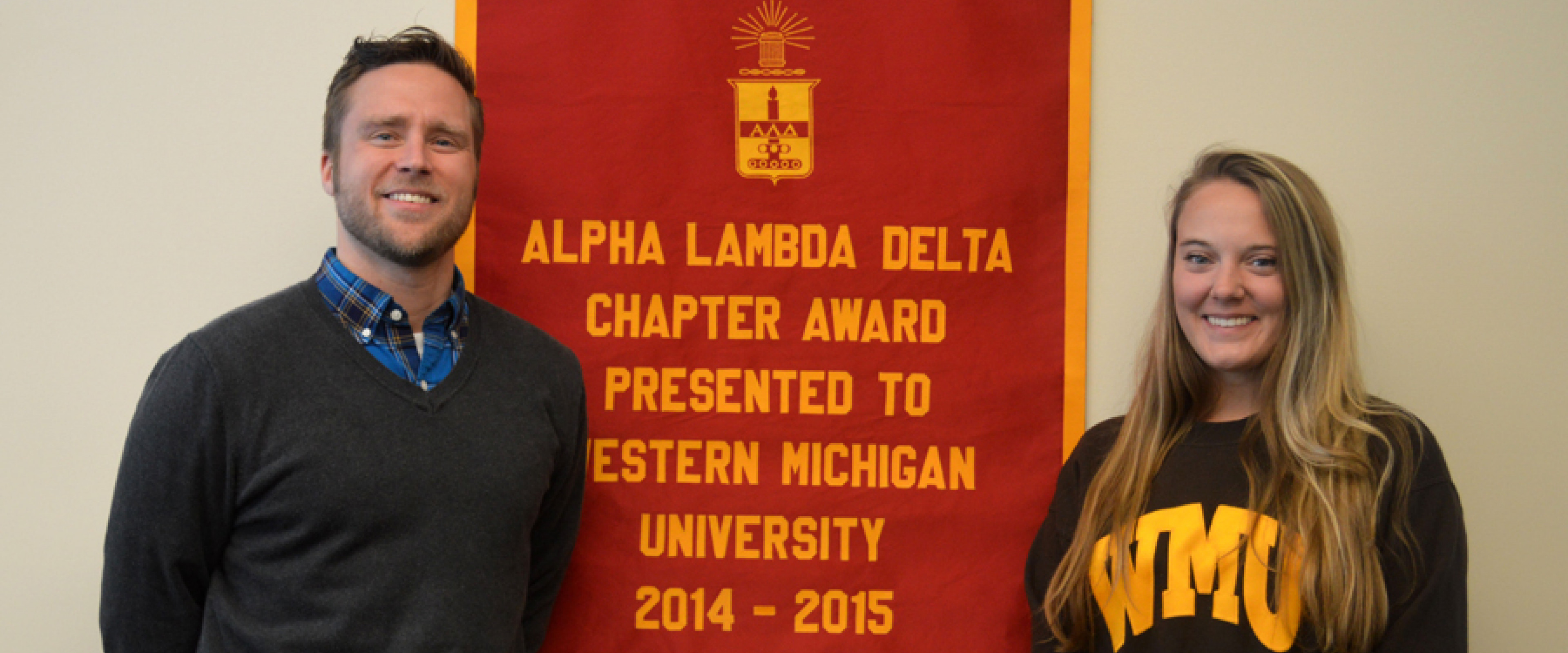 Anthony Helms and Erin Caspers standing in front of an Alpha Lambda Delta banner.