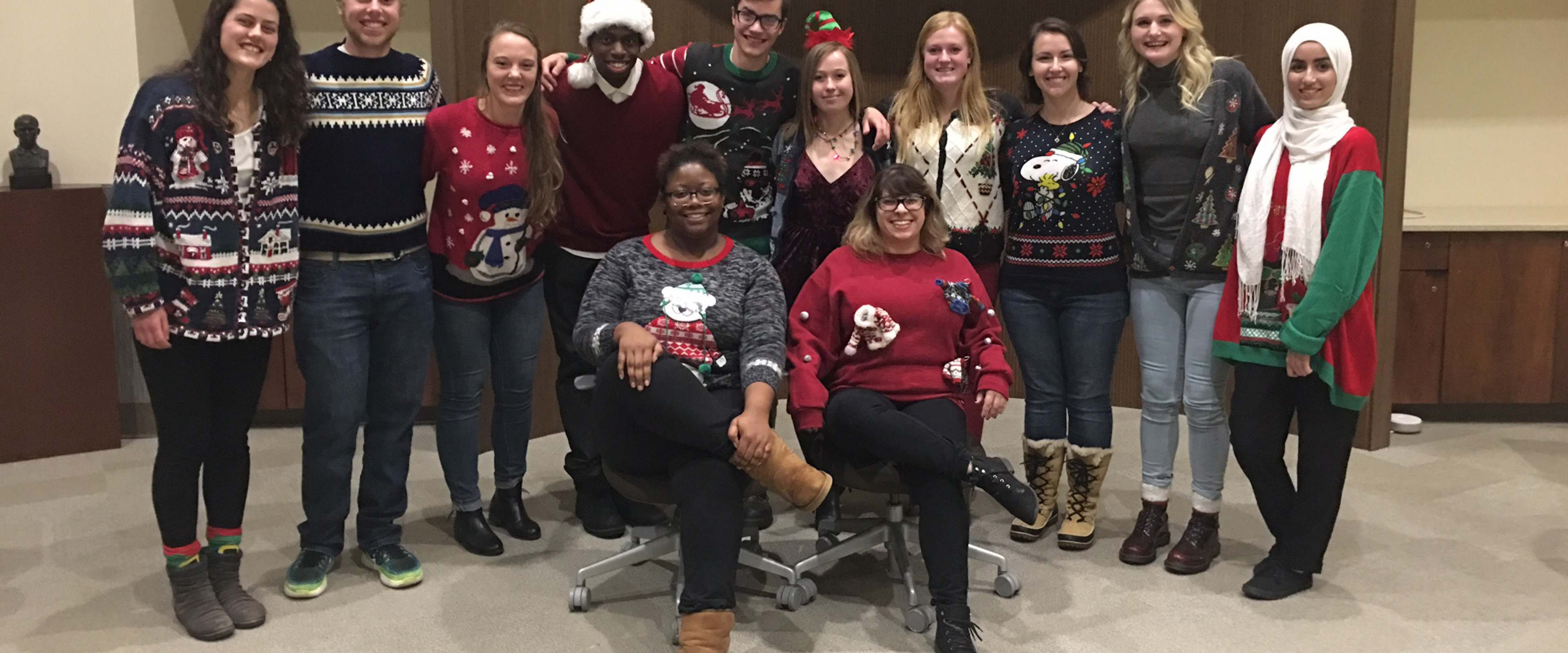 The 2016 Peer Student Success Team mentors wearing holiday sweaters in the honors college lounge.