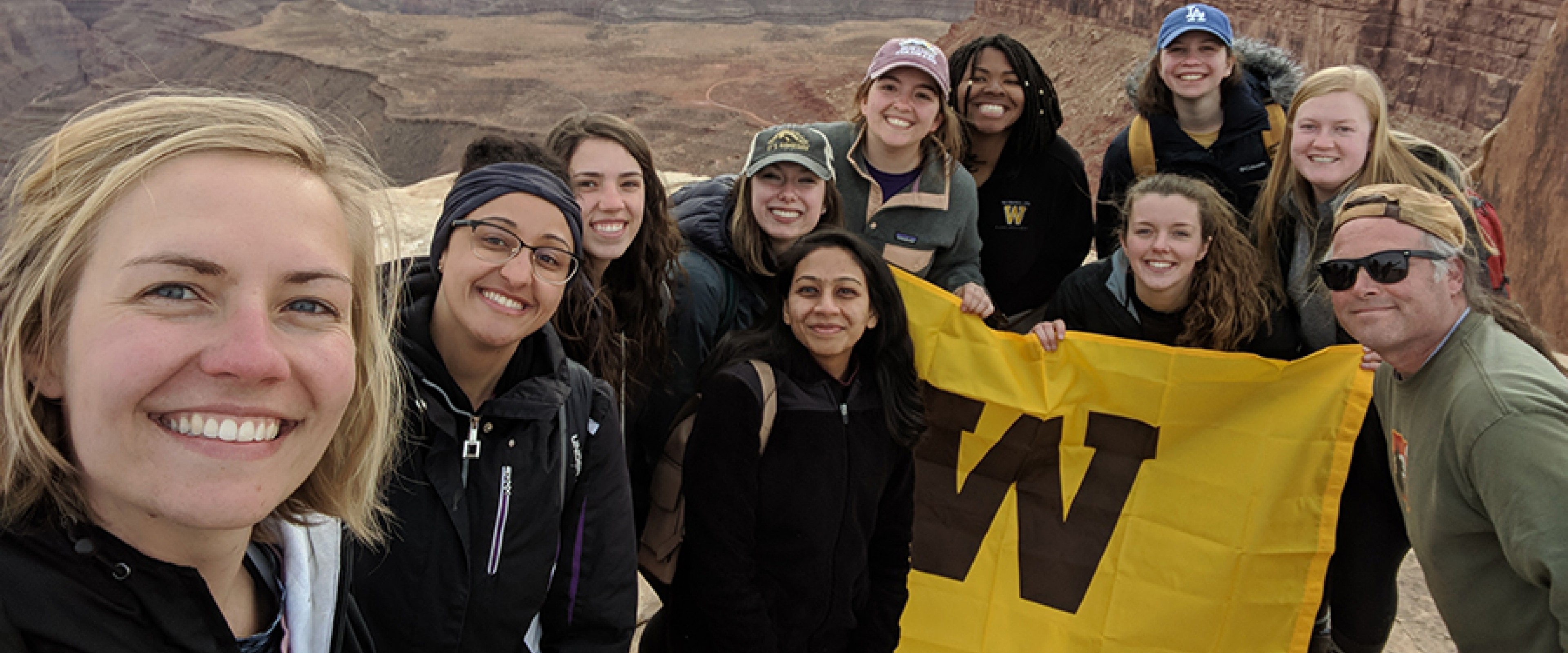 Honors college students and instructor Jeff Johnson stand in front of a canyon holding a WMU flag.