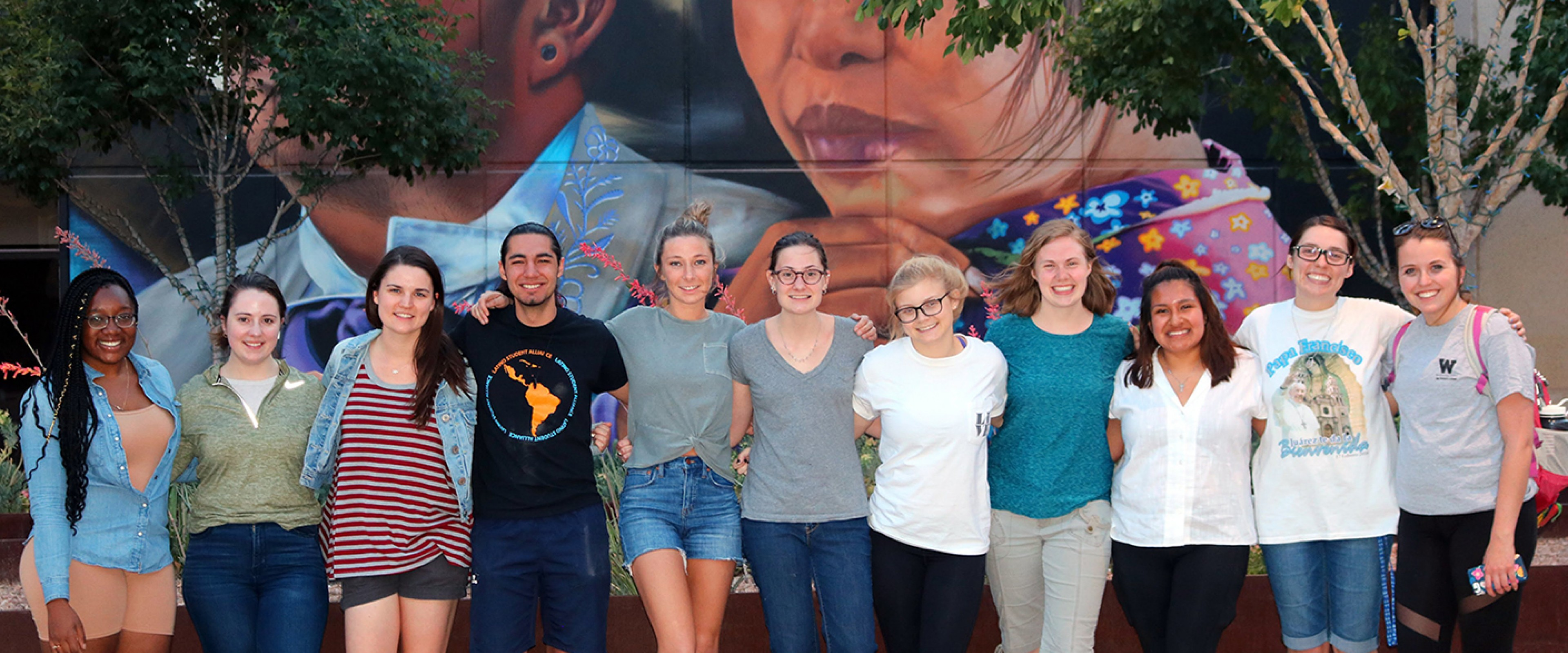Honors students linking arms in front of a mural.