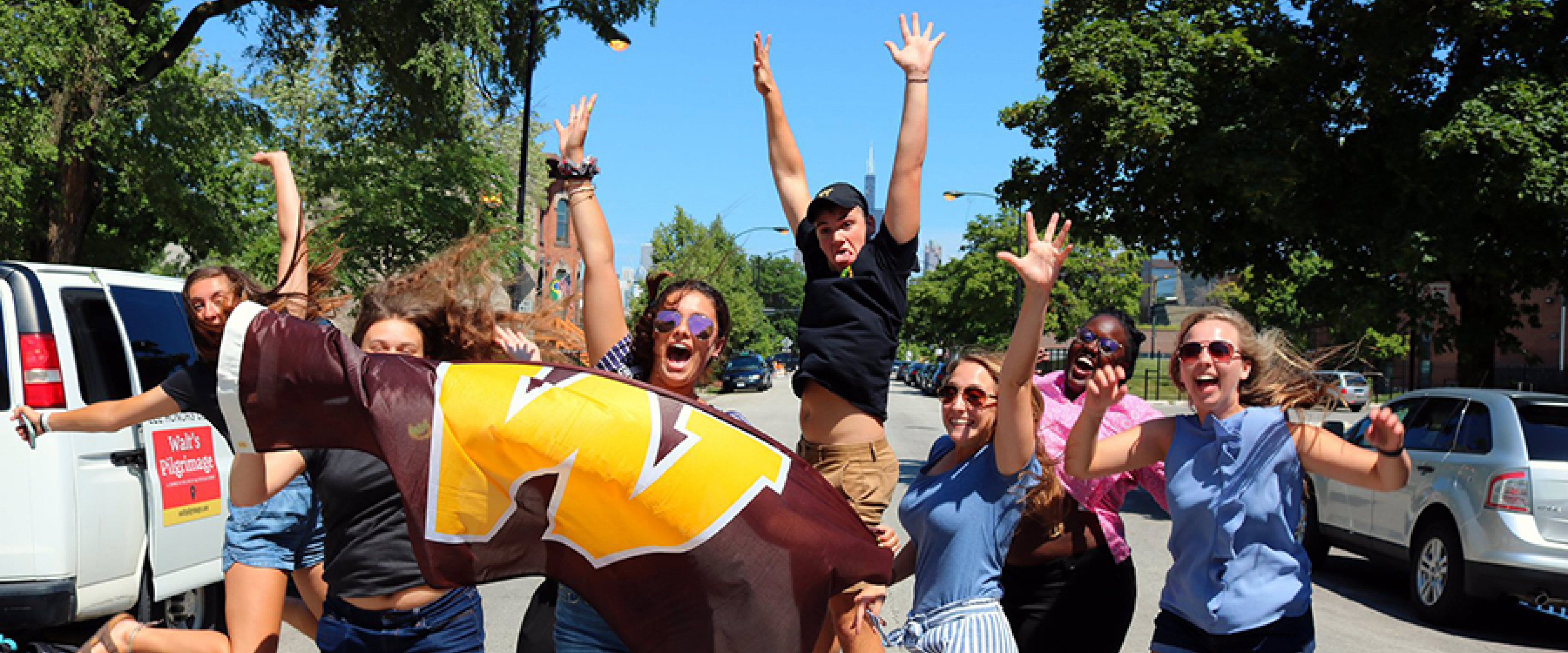 Students on the Walt's Pilgrimage trip jumping with a WMU flag.