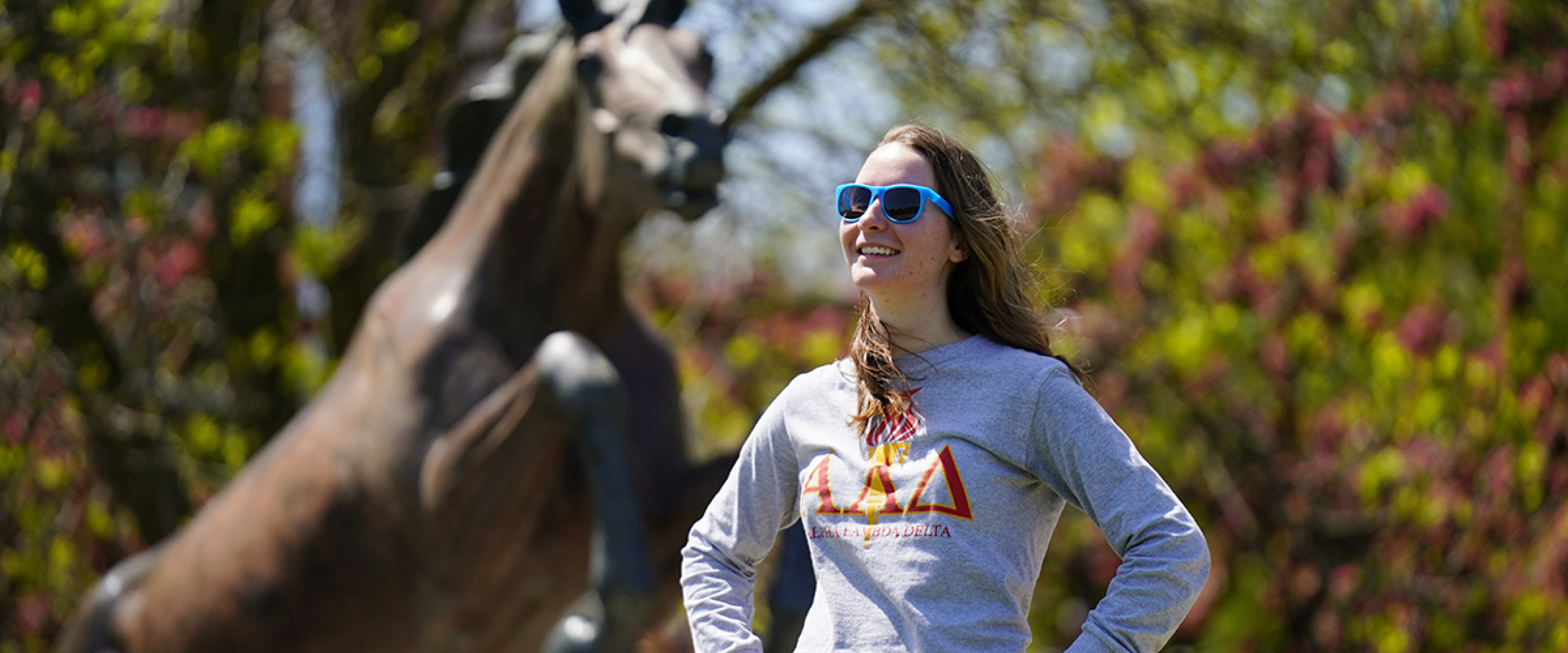 A student wearing an ALD shirt standing in front of the Bronco statue.