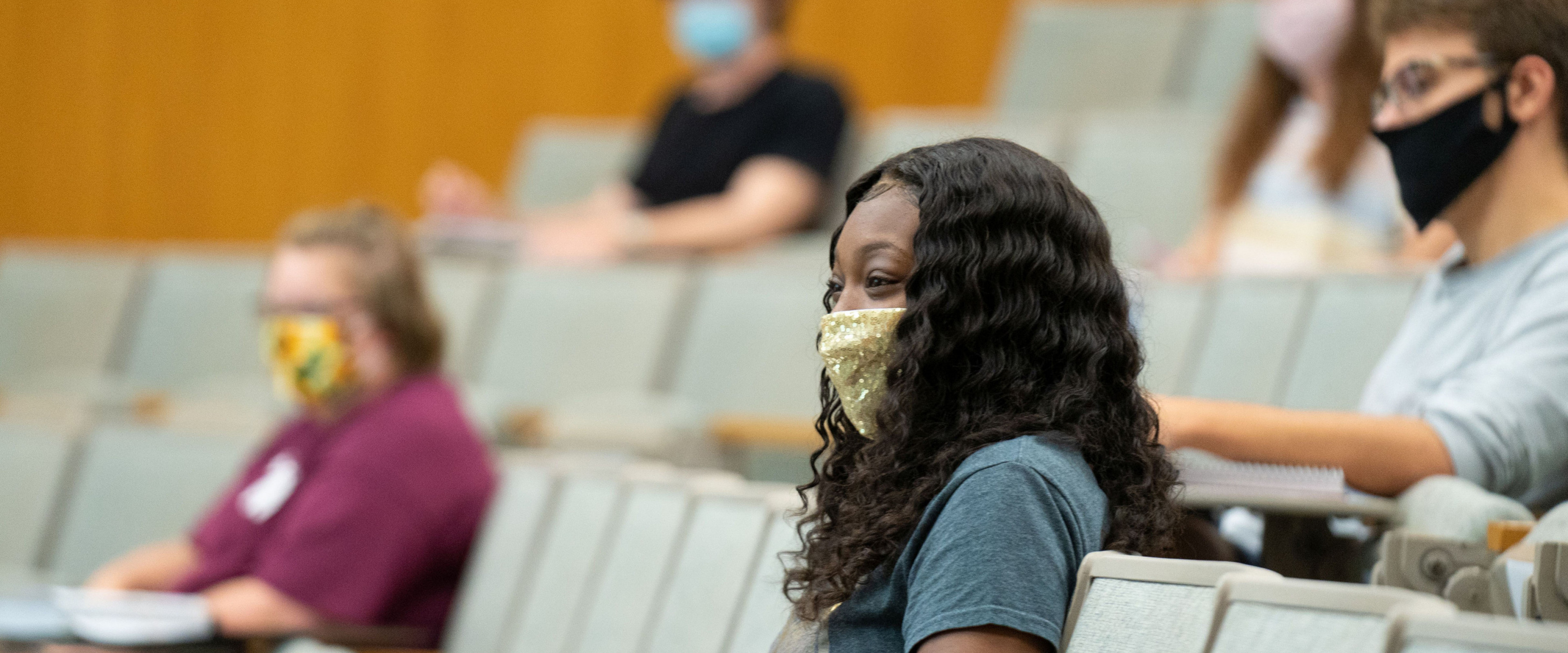 Socially distanced students sitting in auditorium wearing face masks