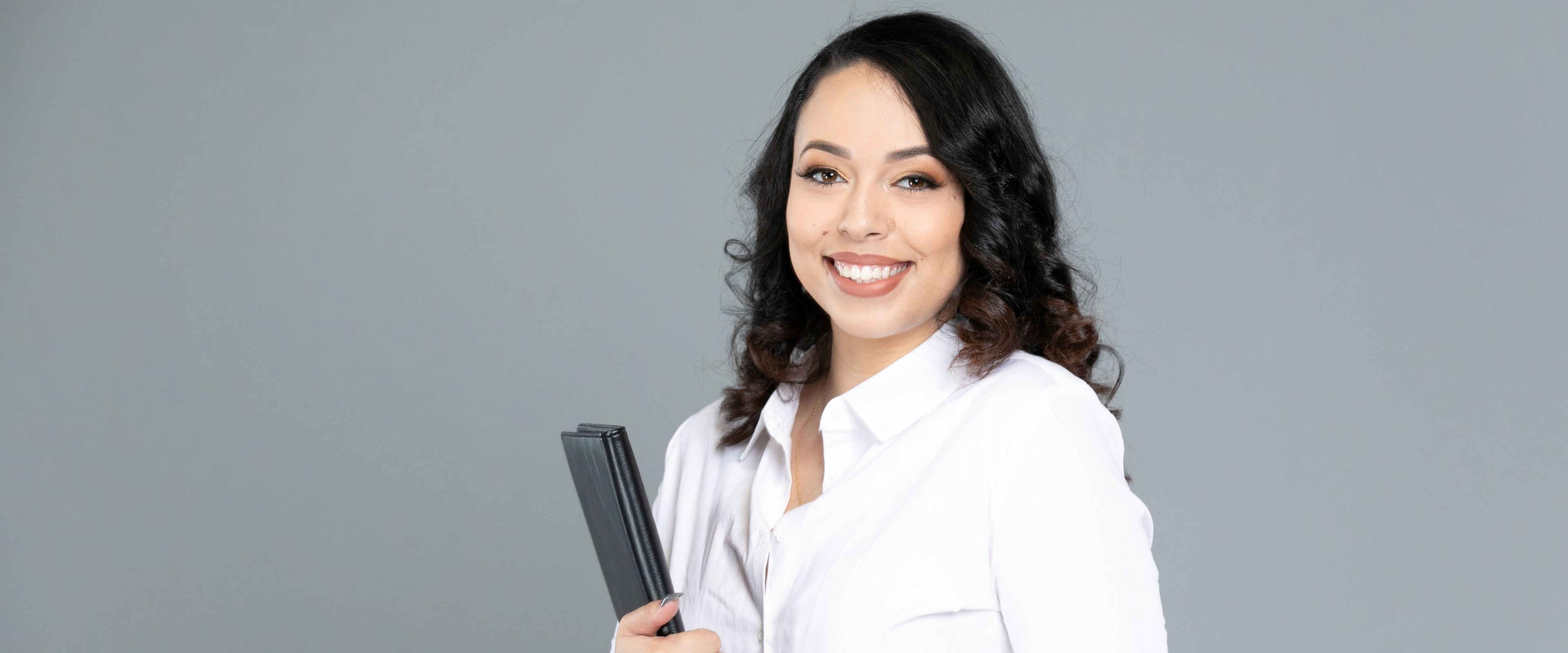 Pictured is a student smiling and holding a portfolio