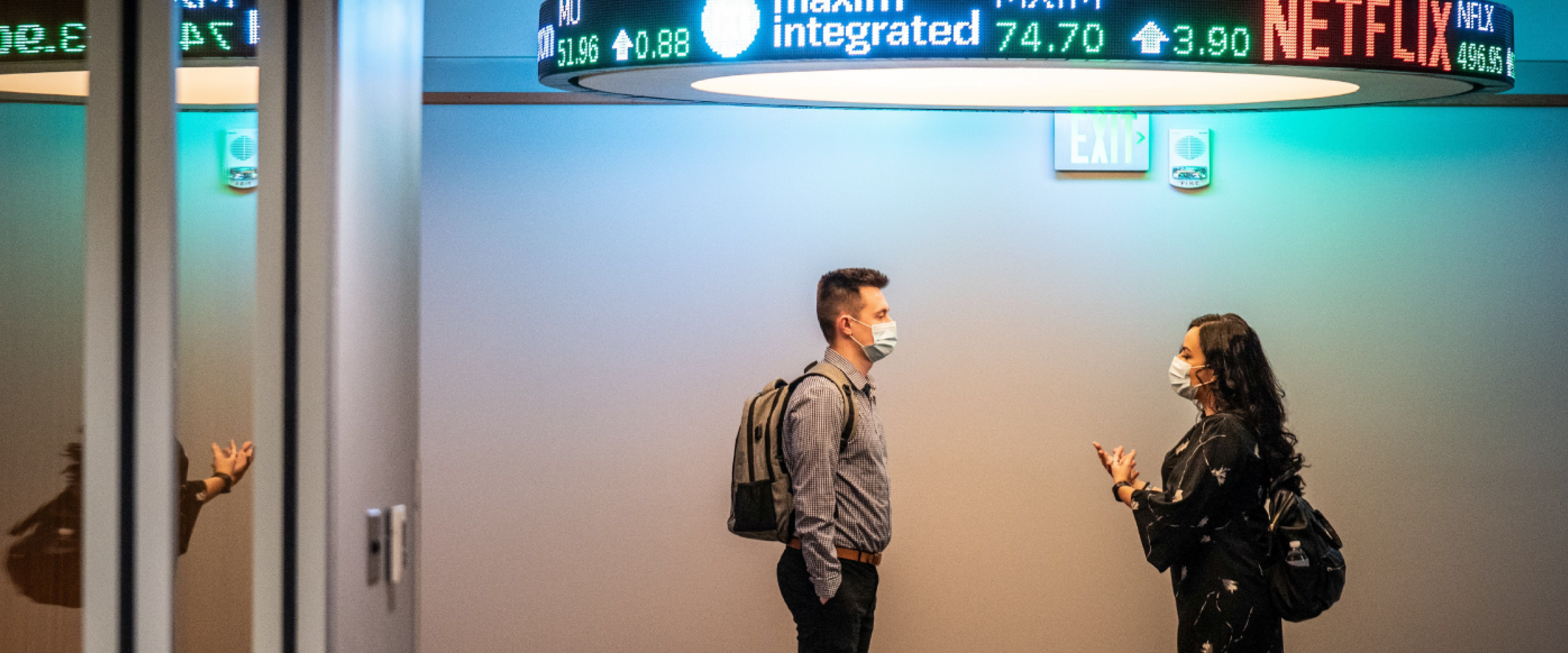 Two masked students standing in hallway under stock ticker