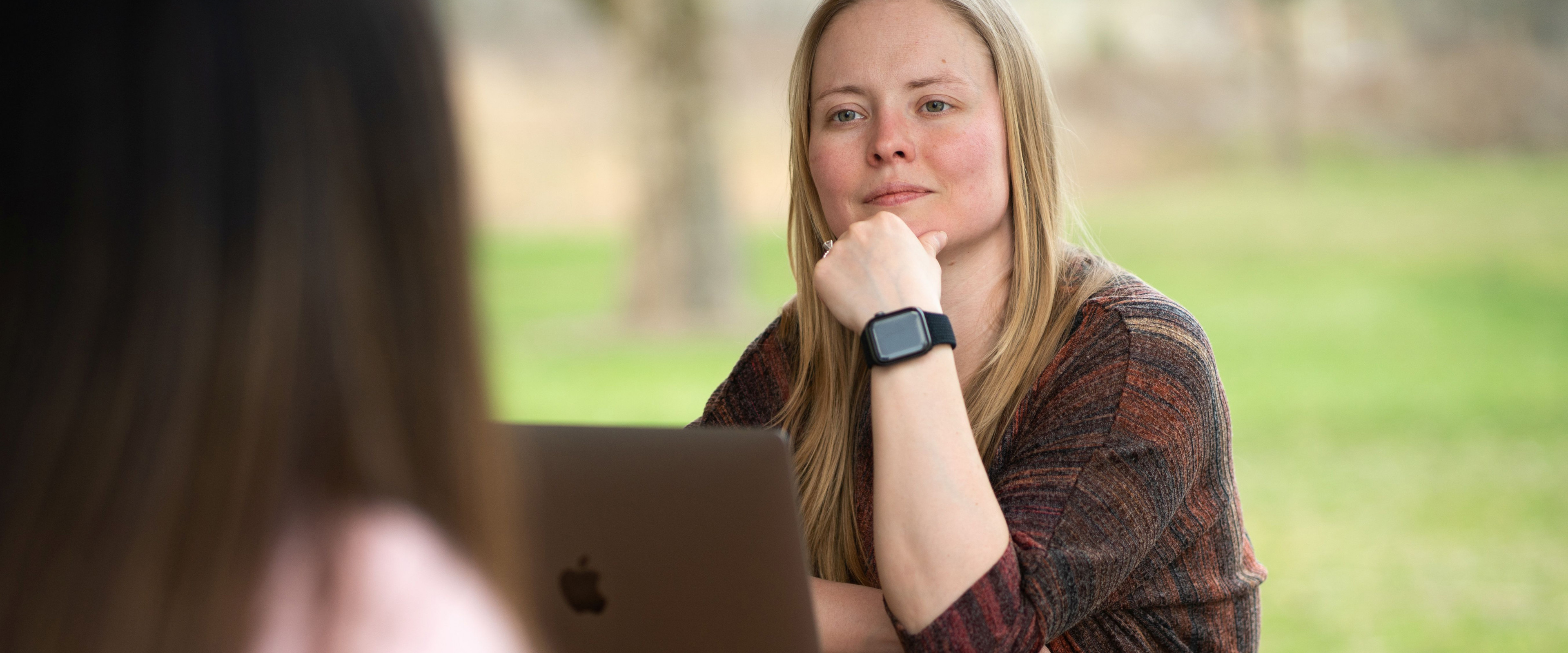 Katie Marshall sitting at laptop, resting her face on her hand.