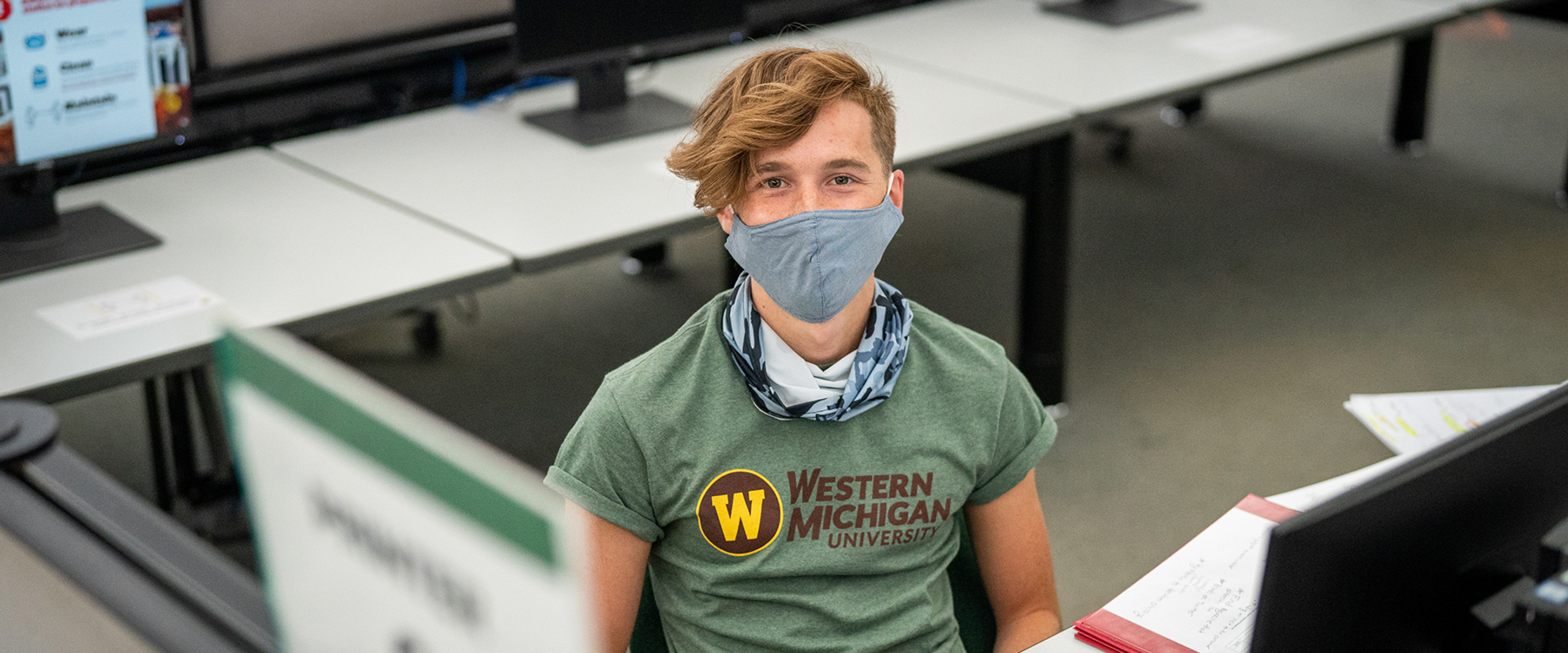 Student sitting in front of a computer wearing a mask