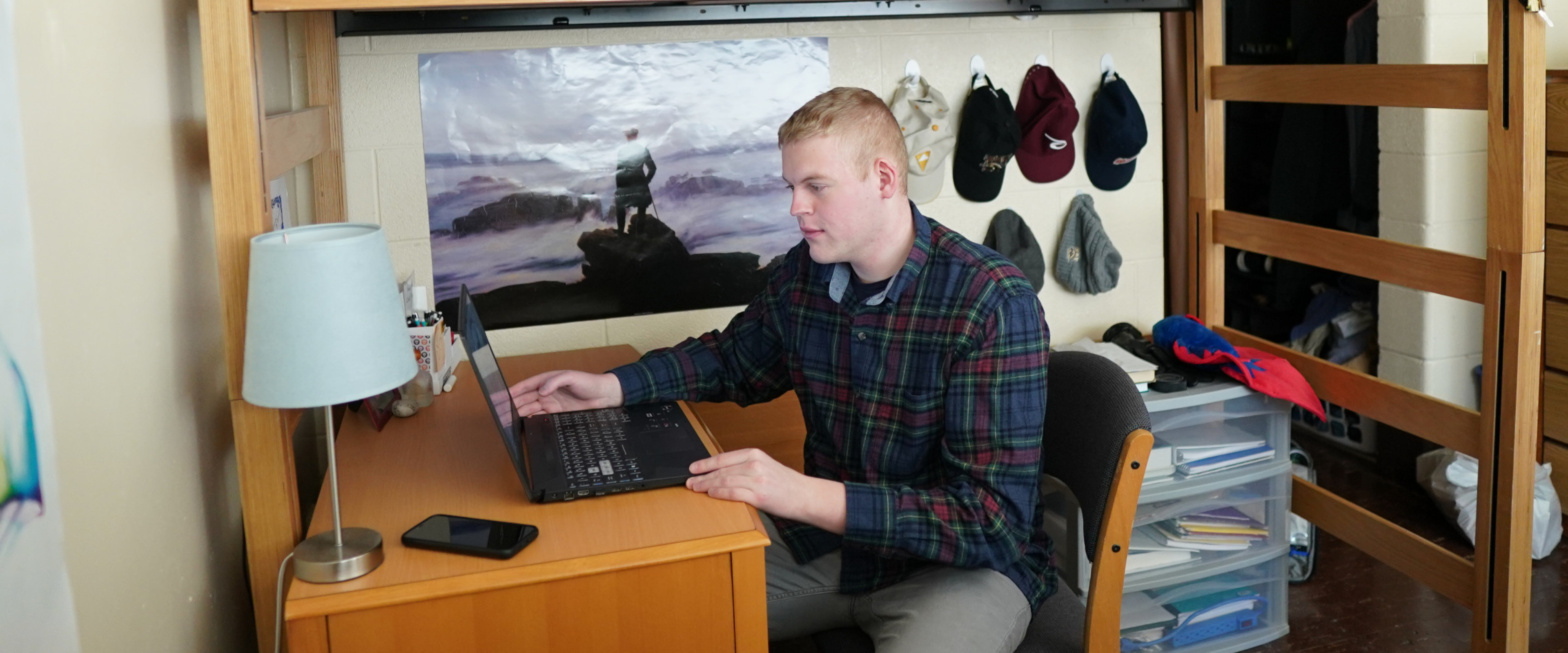 Student sitting at desk with laptop in their residence hall room