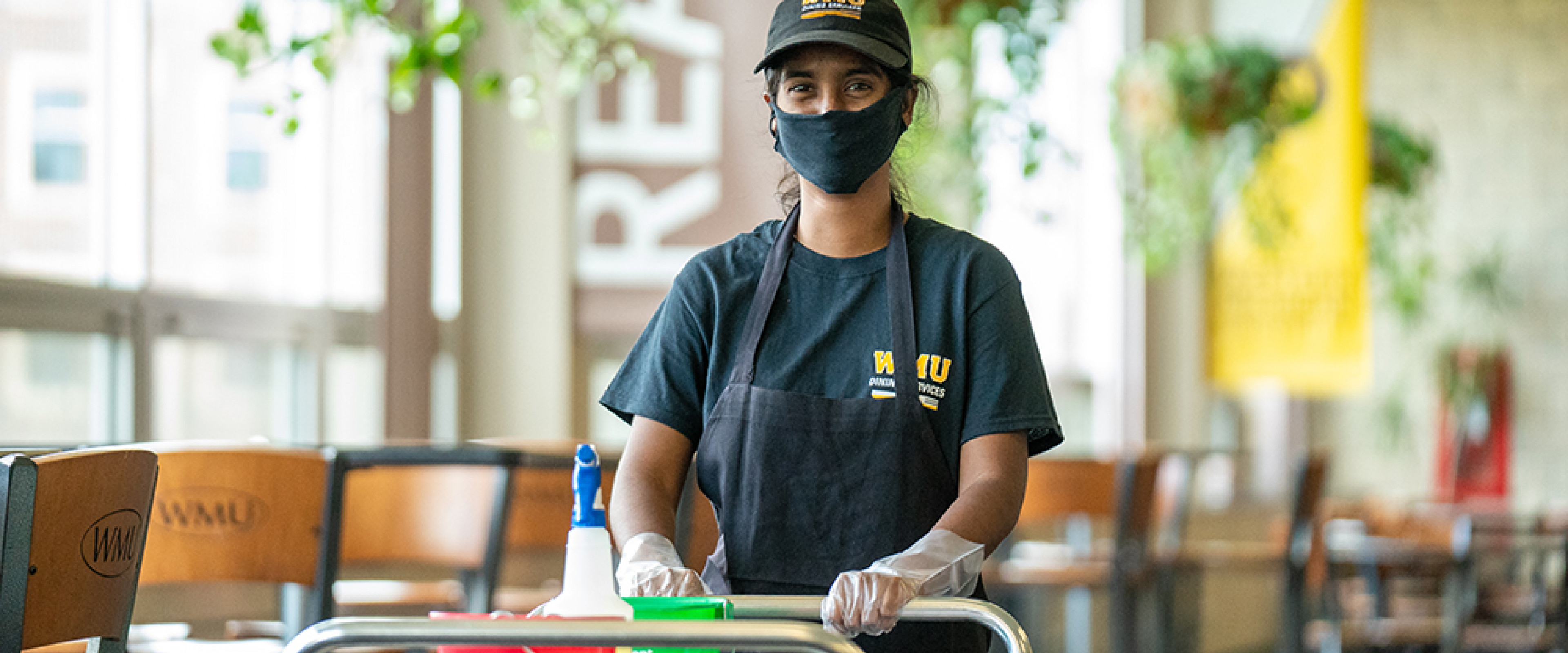 Student employee sanitizing tables in the dining center