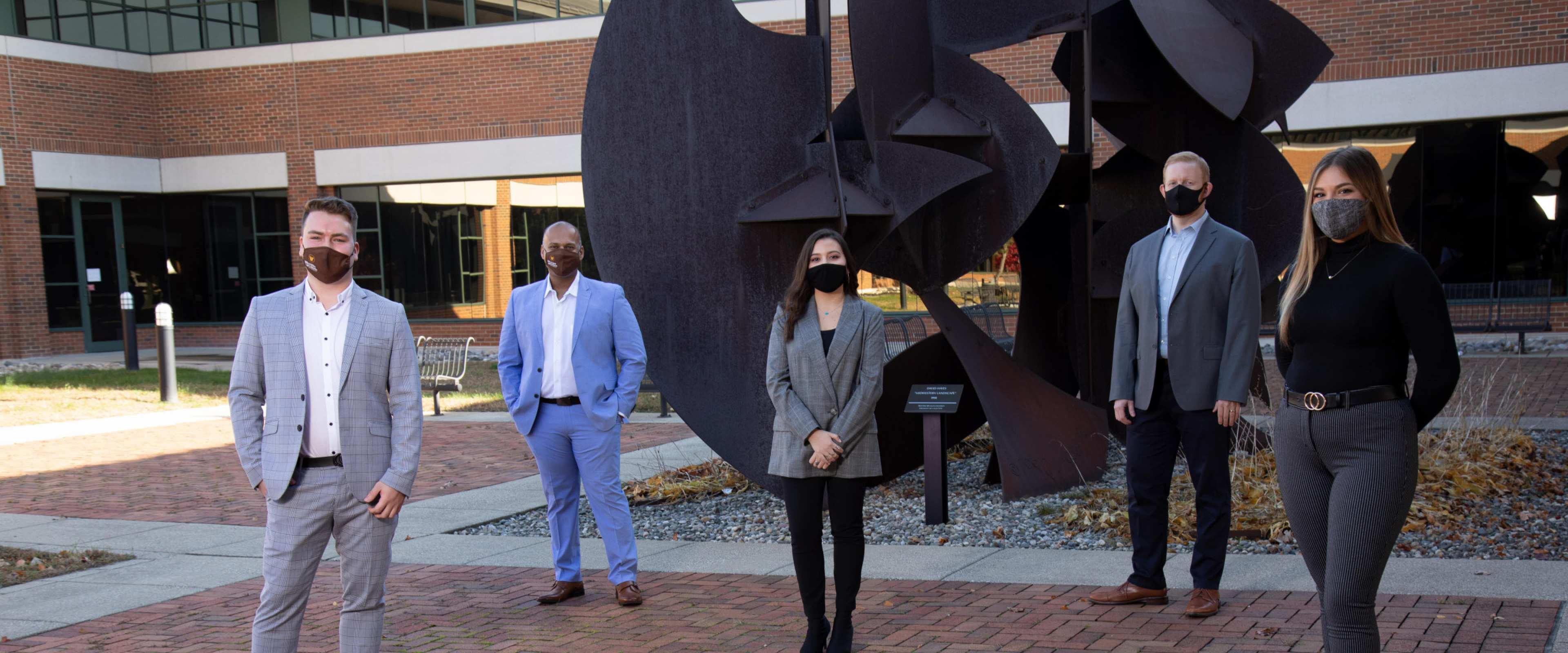 Three students, and two faculty members, masked, stand in the WMU Haworth courtyard,