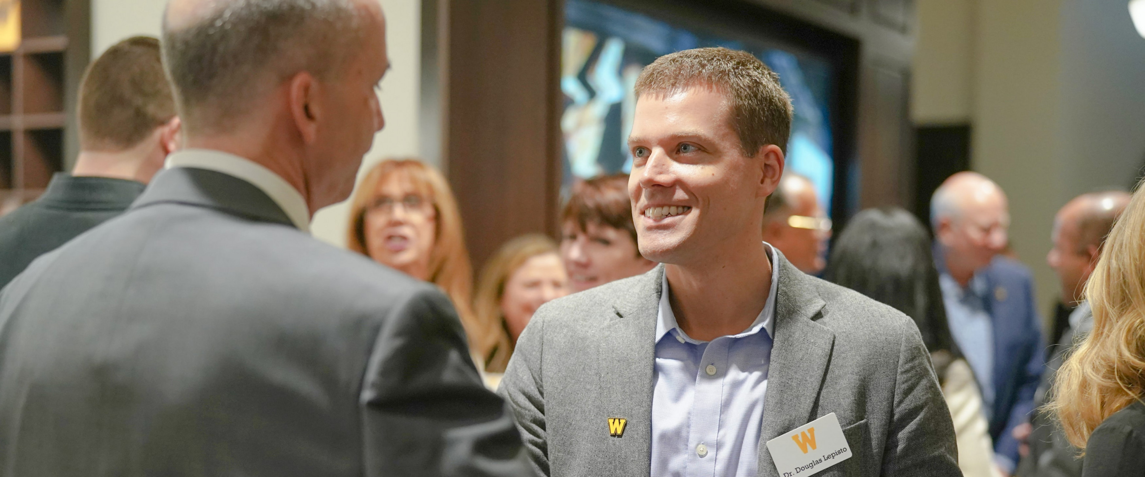 Dr. Doug Lepisto, shakes hands, before the COVID-19 pandemic, at a WMU Haworth event.
