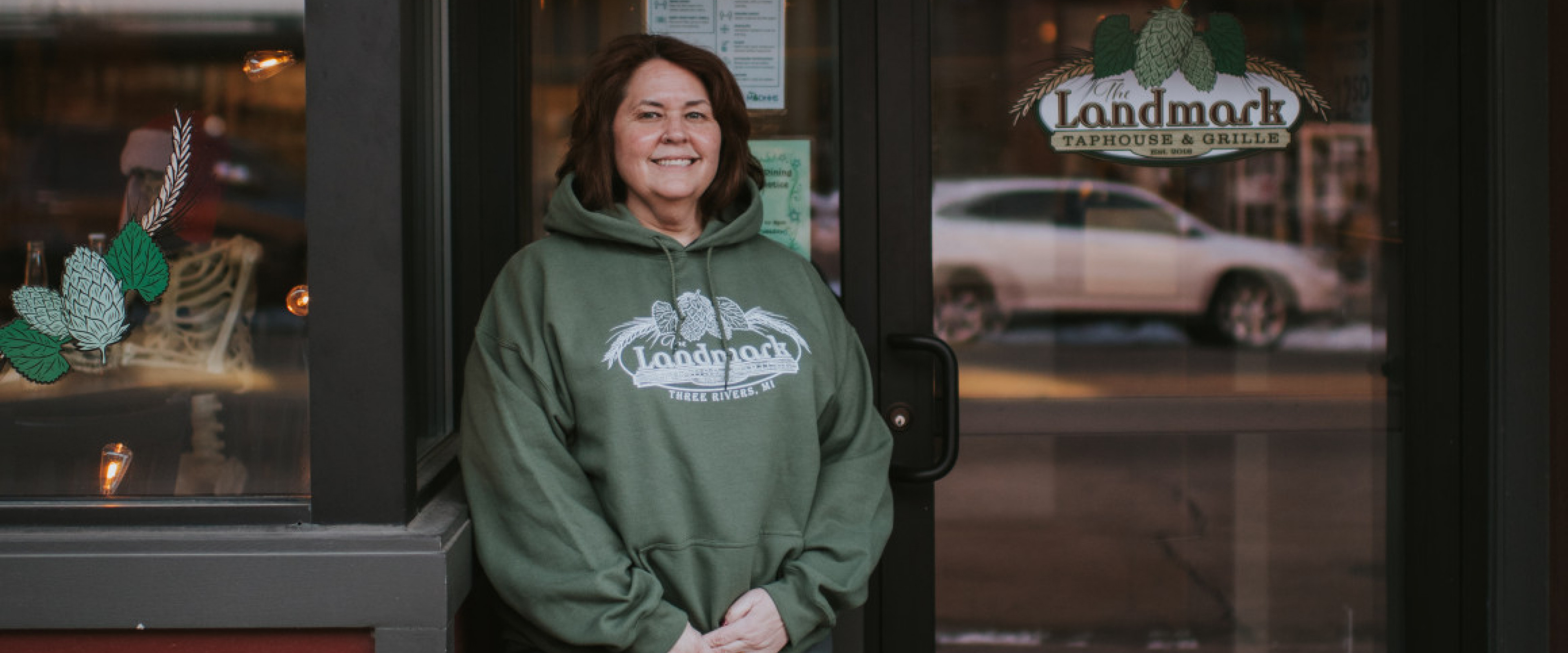 Nancy Russell, owner of the Landmark Taphouse and Grille, smiles in front of her restaurant.