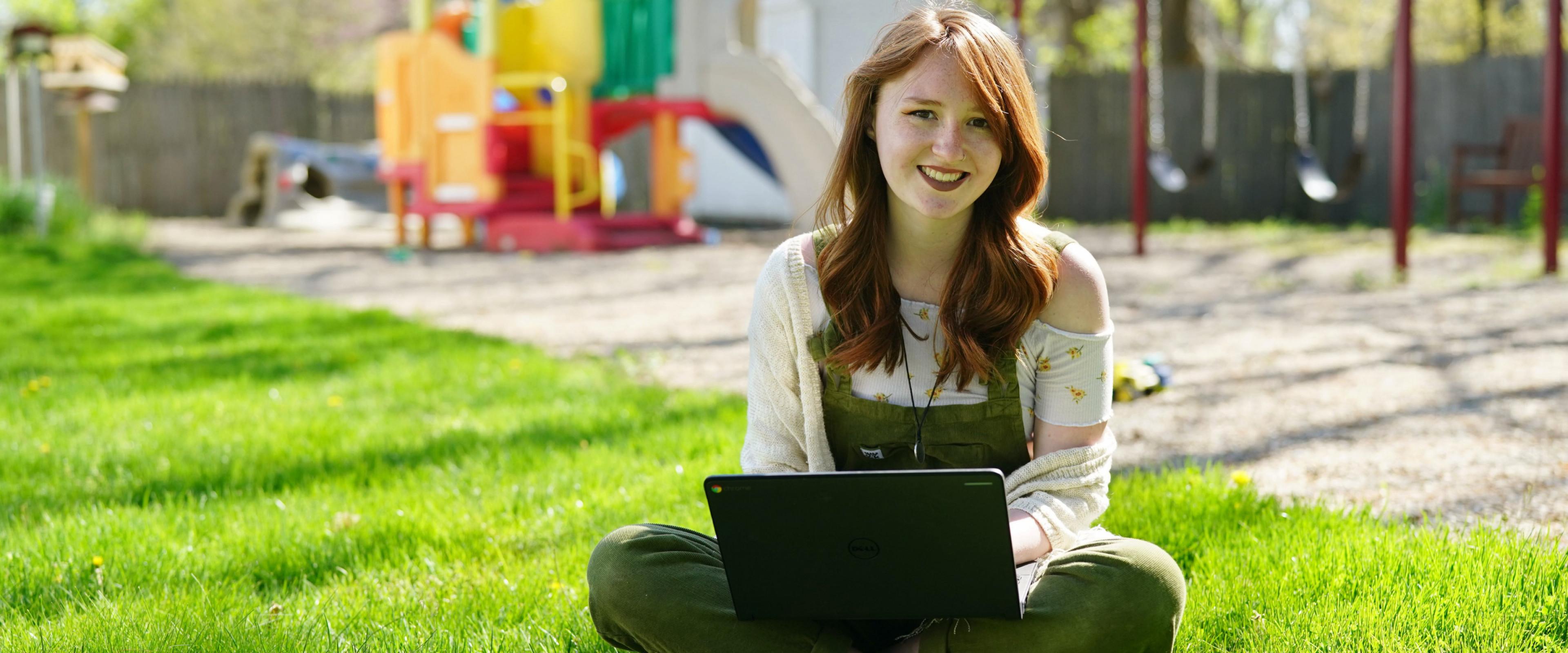 Kirstin Laduke with laptop on a playground