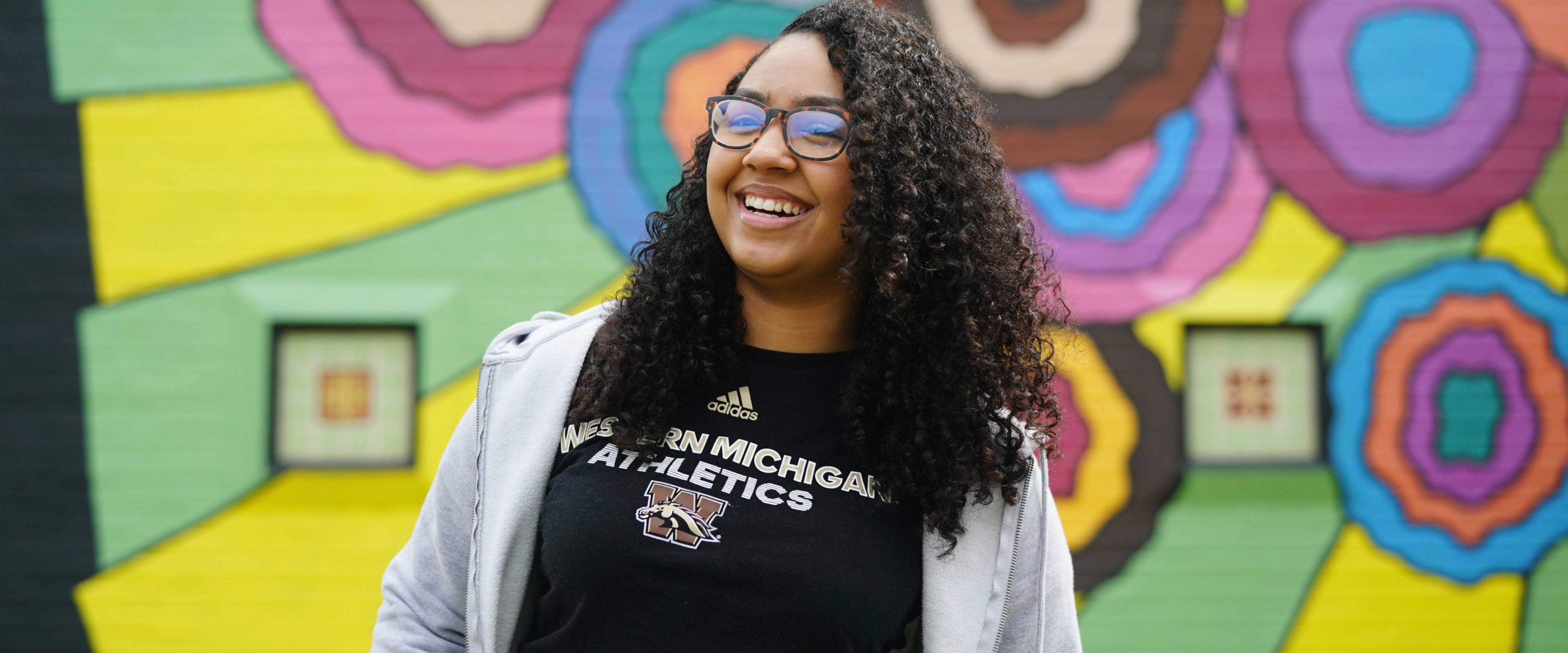 Breyana Wilson in front of colorful mural