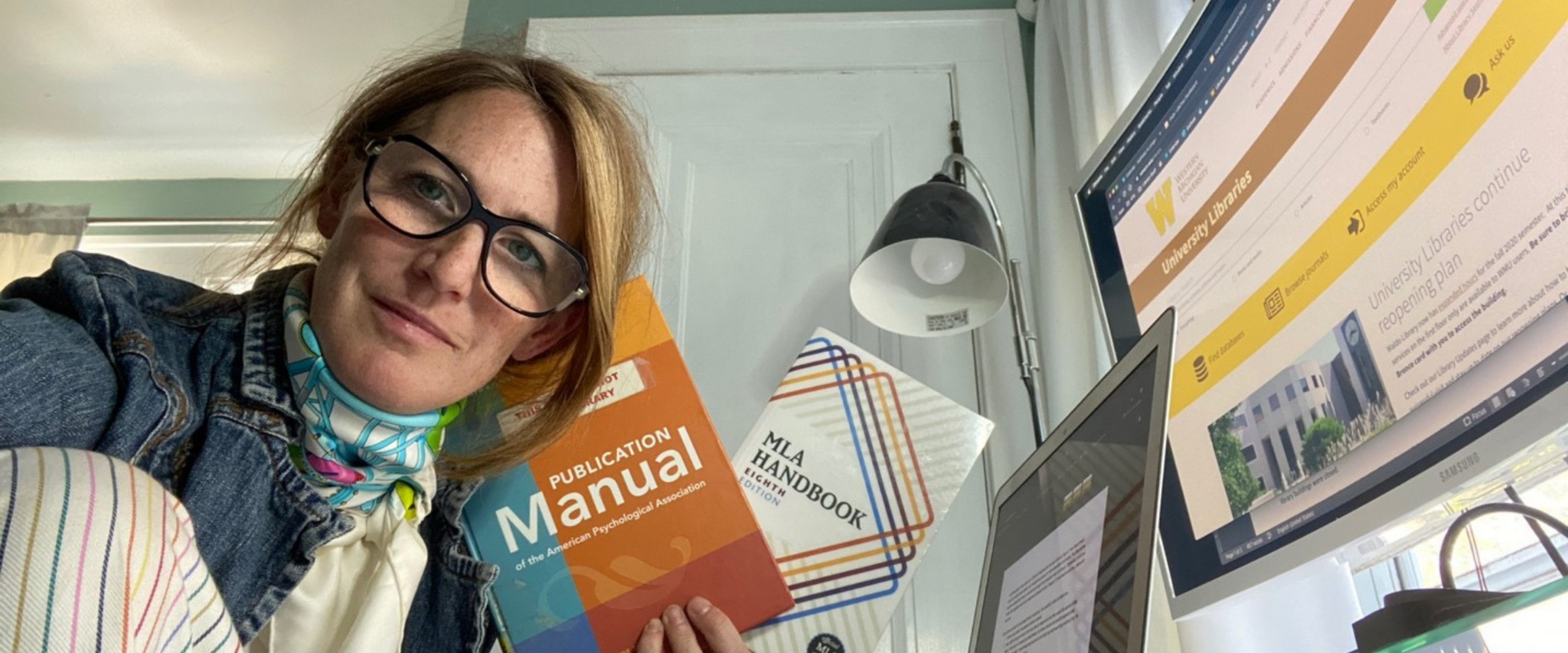 Kate Langan holding the MLA and APA style guides in her home office.