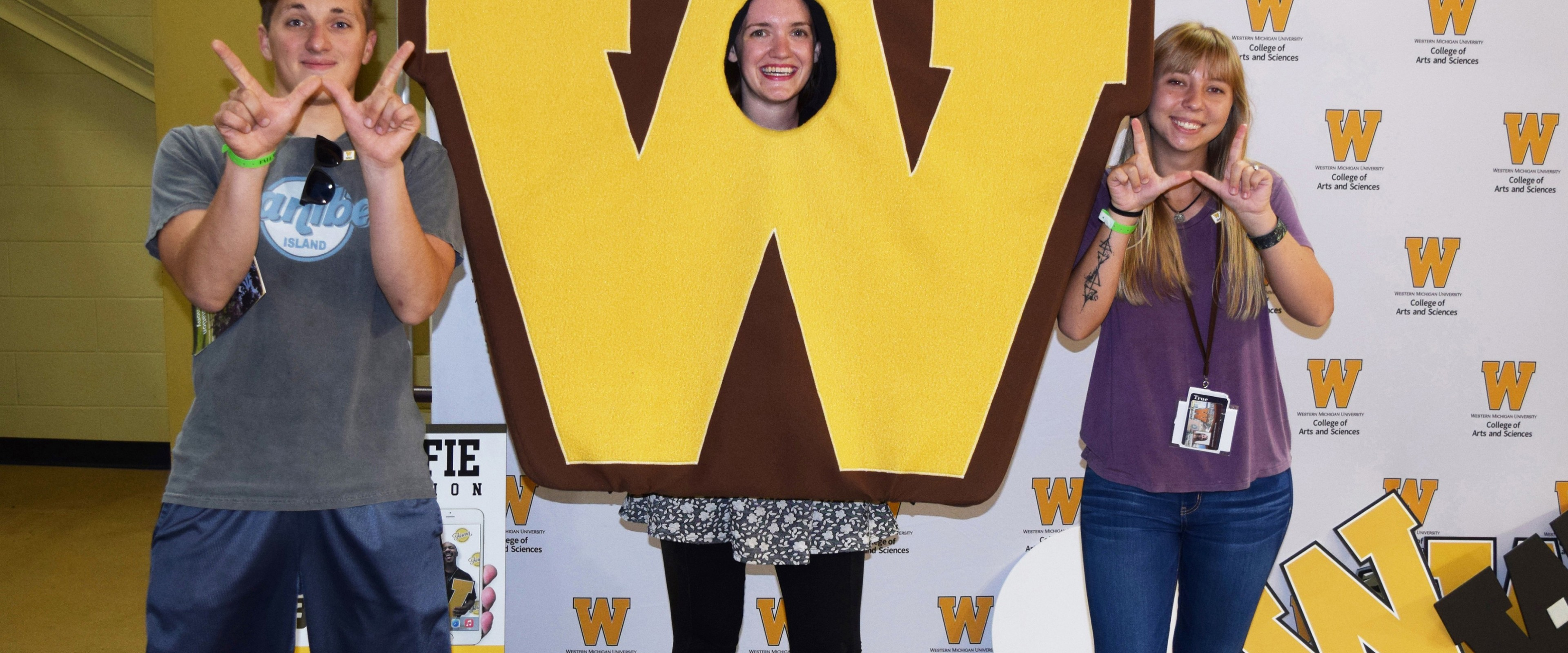 """Students use their fingers to make a """"W"""" symbol at a photoshoot at Fall Welcome"""