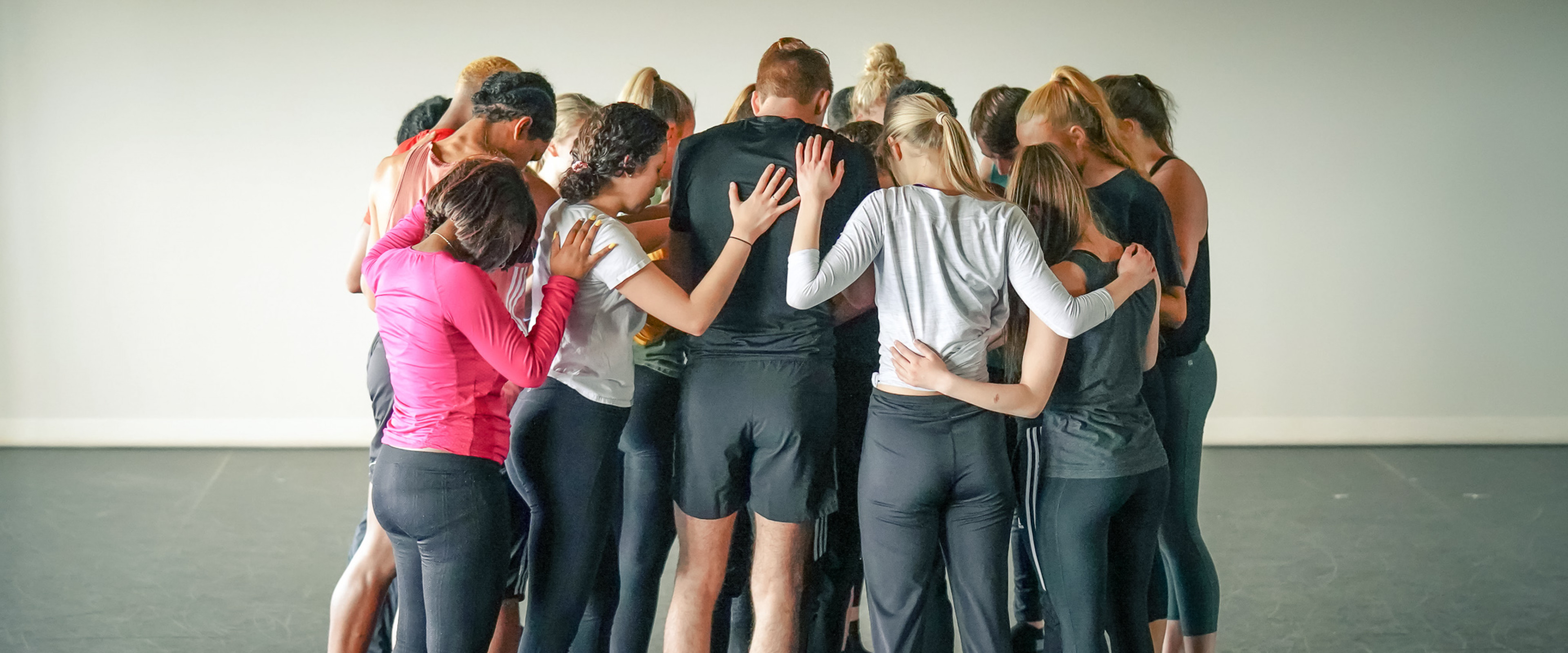 Large group of dancers in a hundle, supporting each other.