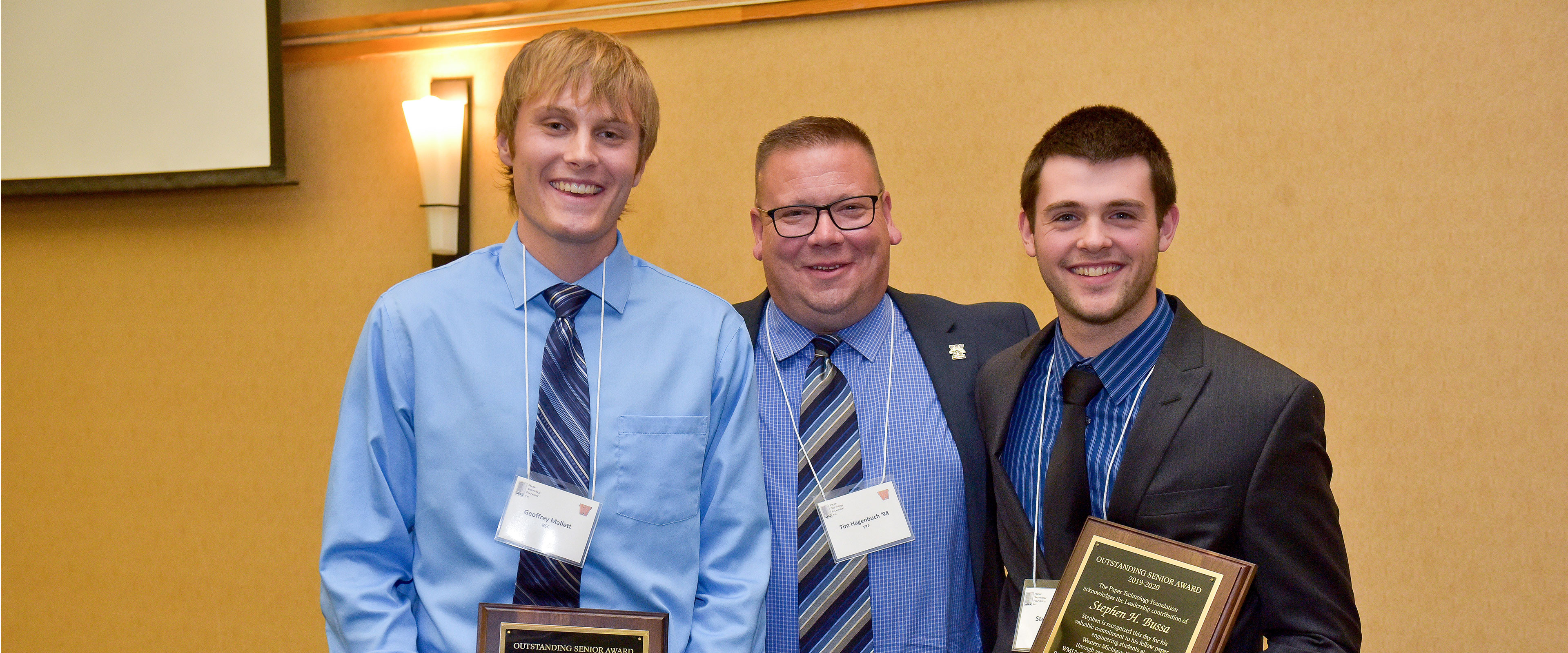 Two student award recipients on either side of Tim Hagenbuch.