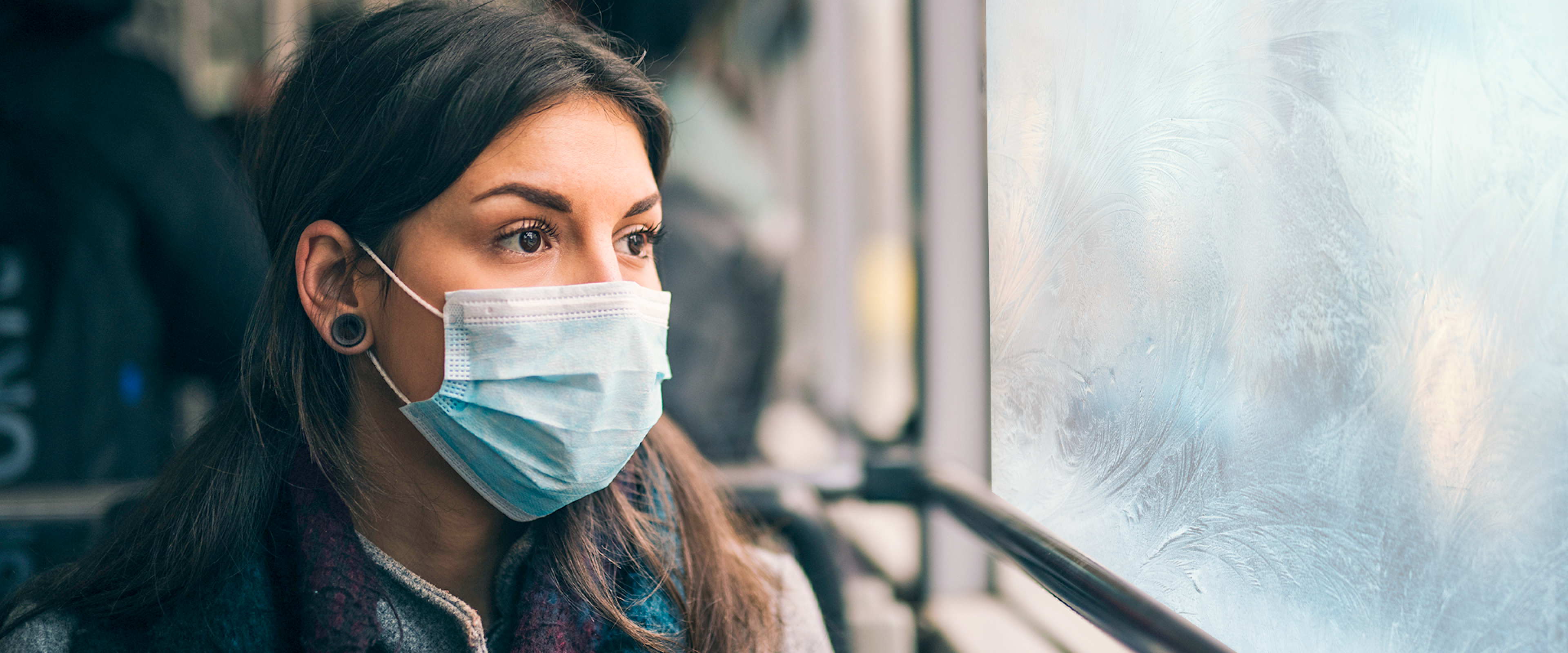 Young lady with winter coat and mask looking out a bus window.