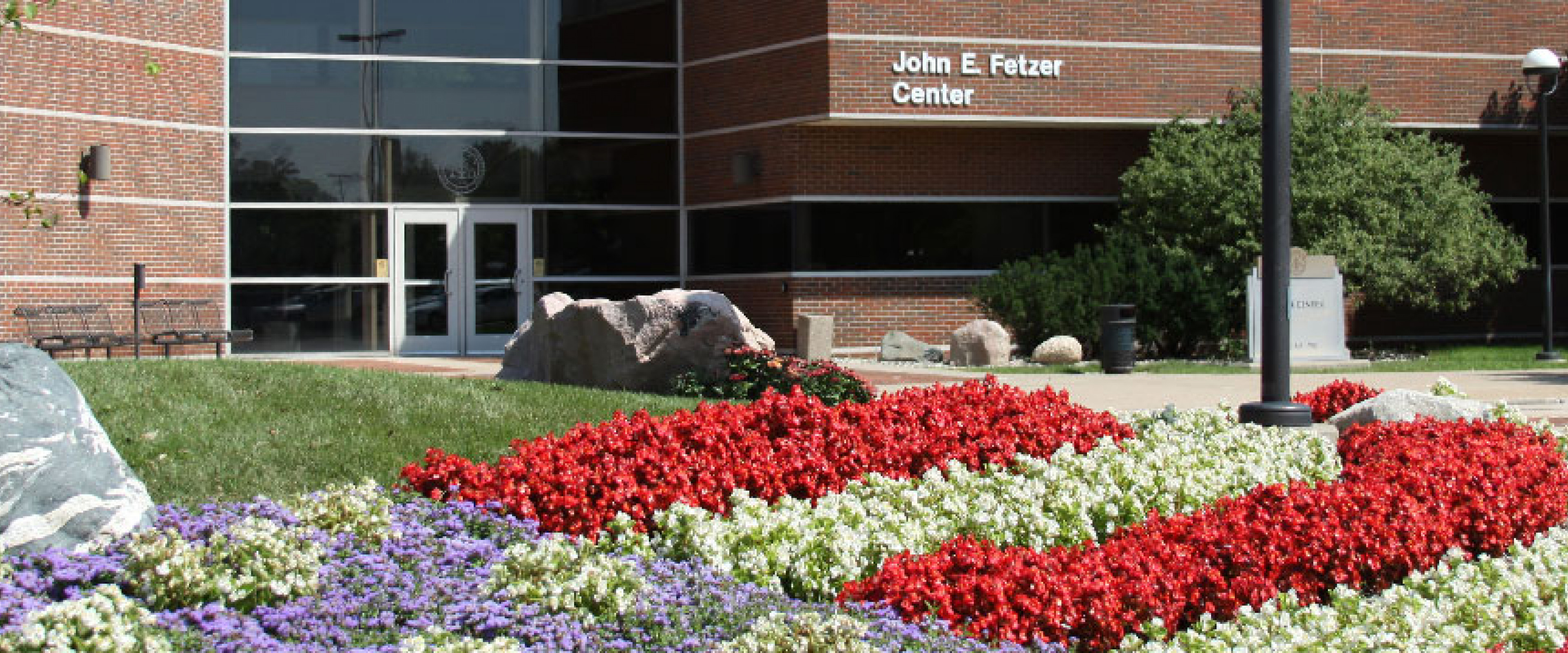 Fetzer building with purple, red and white flowers in front.