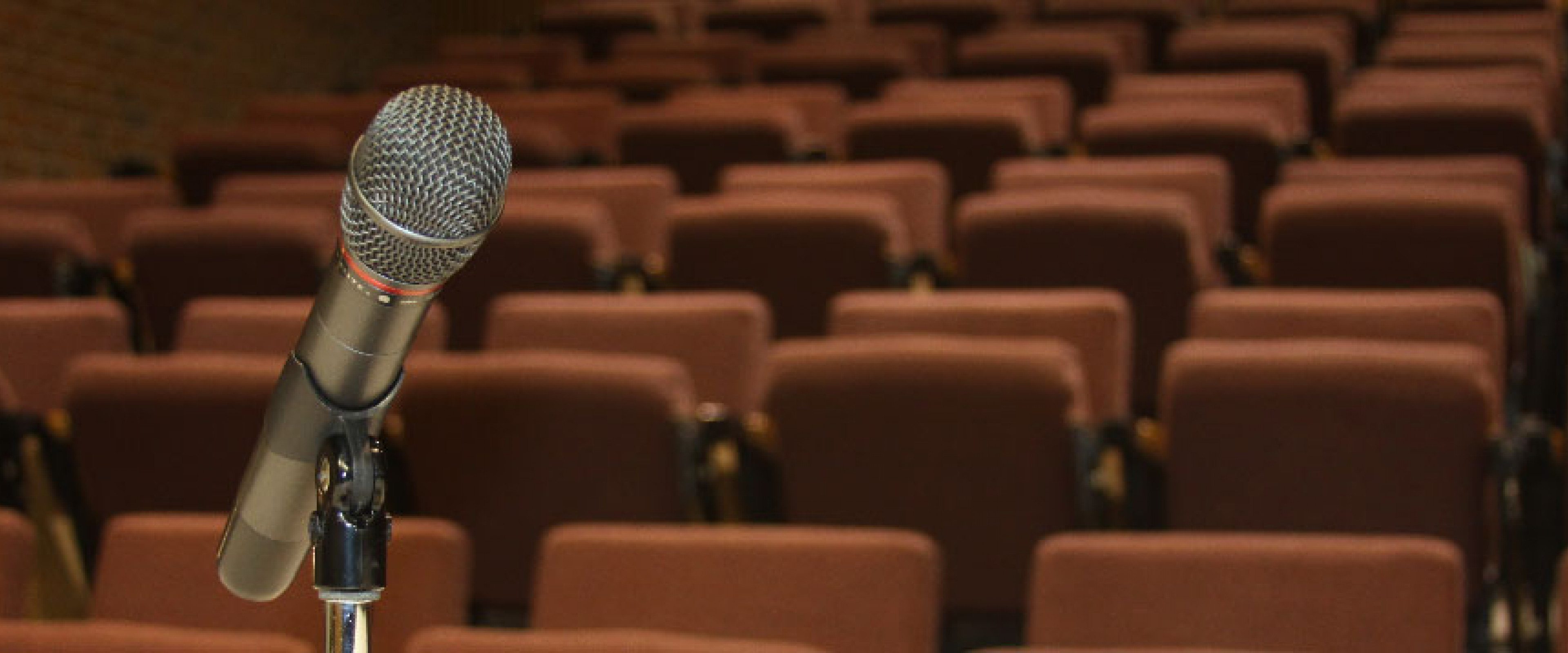 Microphone closeup with auditorium seating in the back