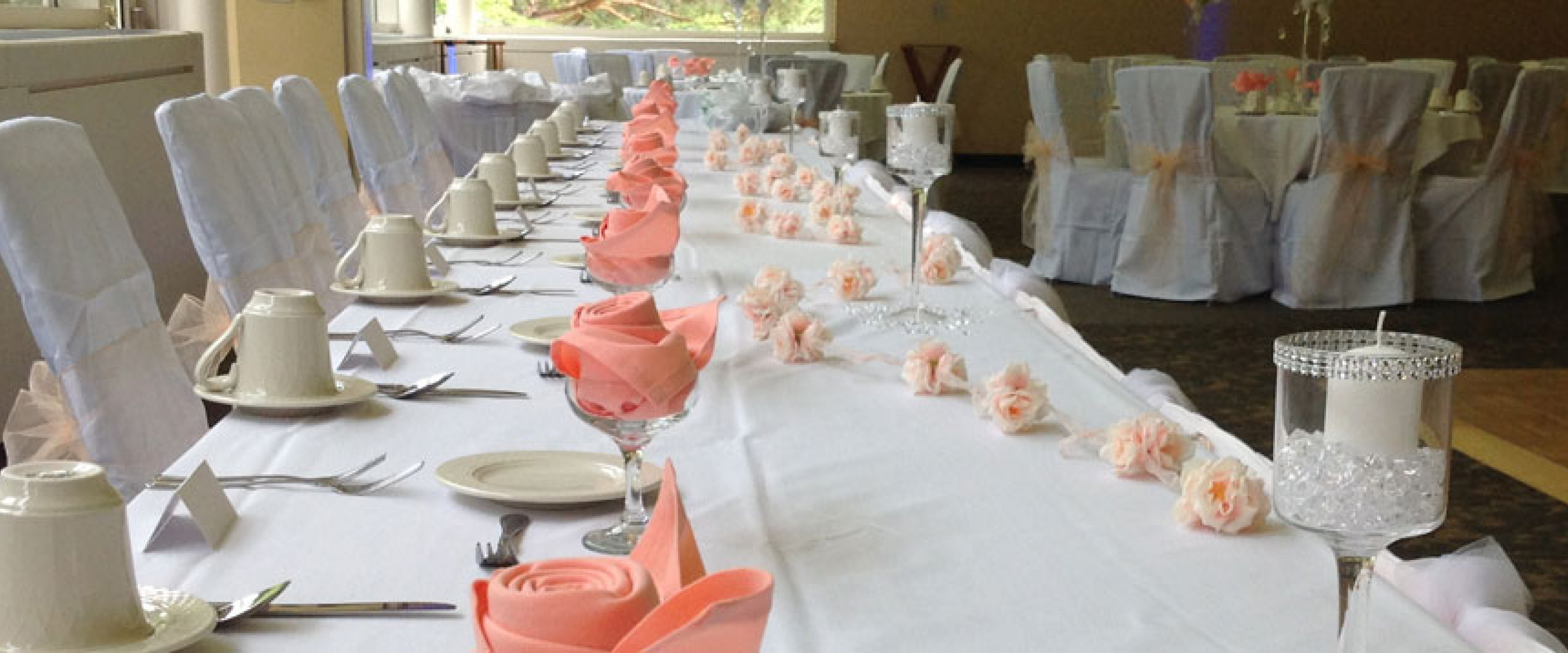 Long front table with white linens and orange napkins in a rose folder inside a wine glass