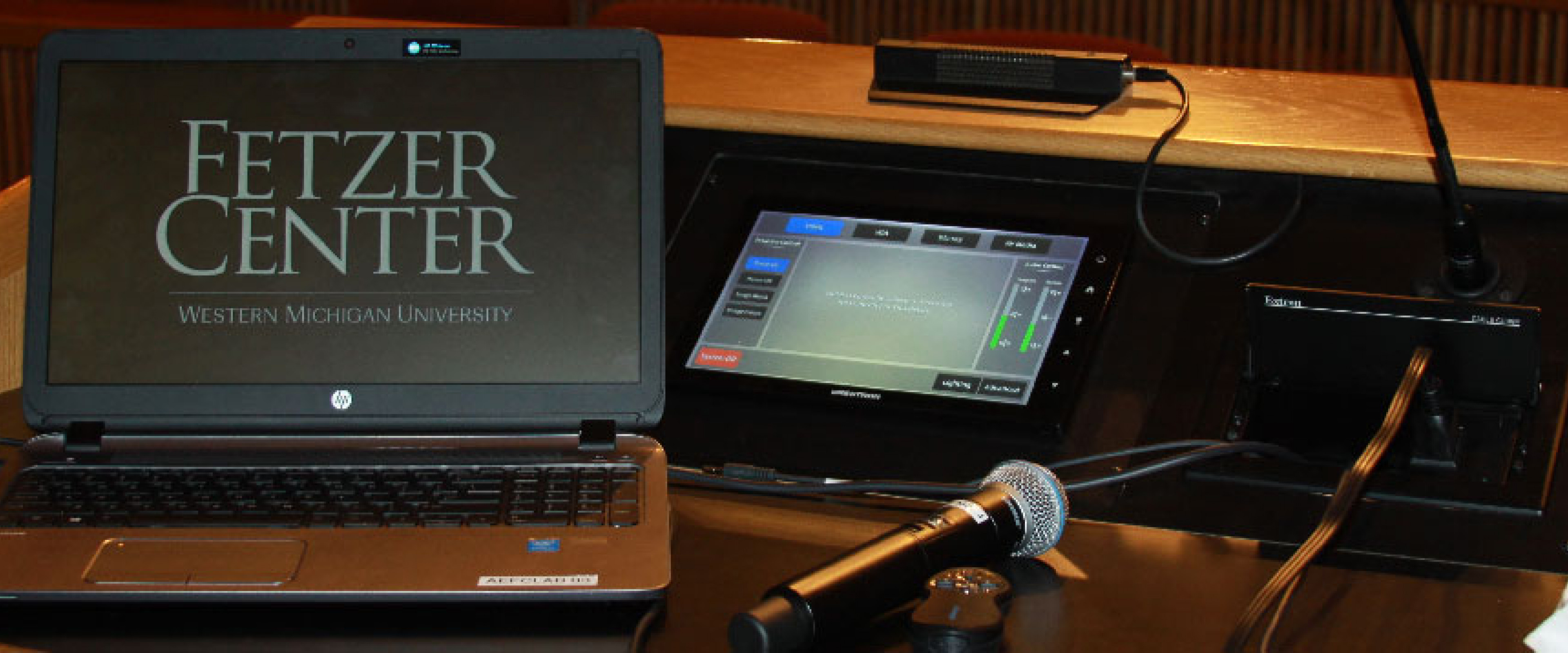 A laptop with Fetzer Center screen savor on a podium with microphone