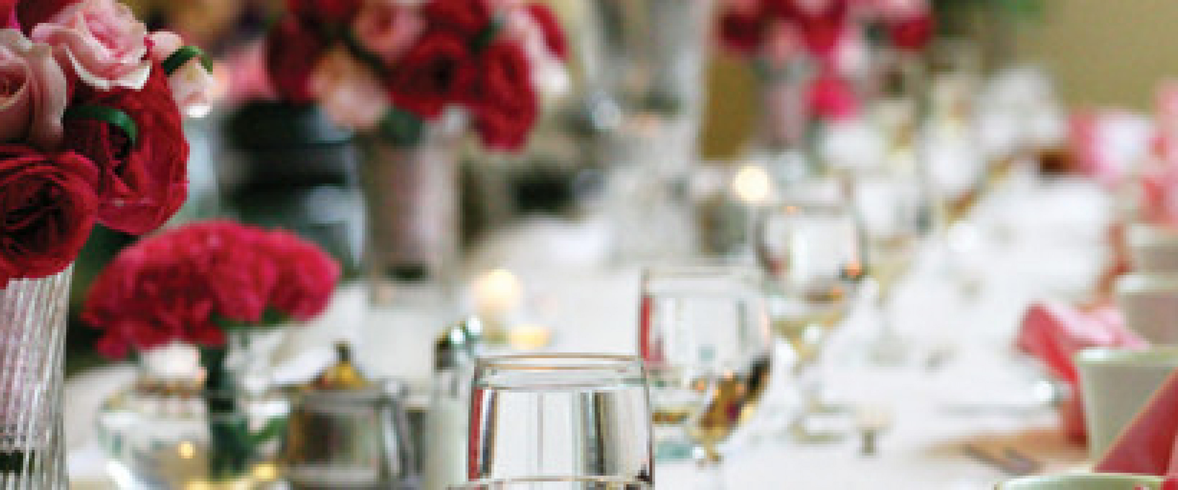 Roses on a head table with white linens, pink napkins with table setting
