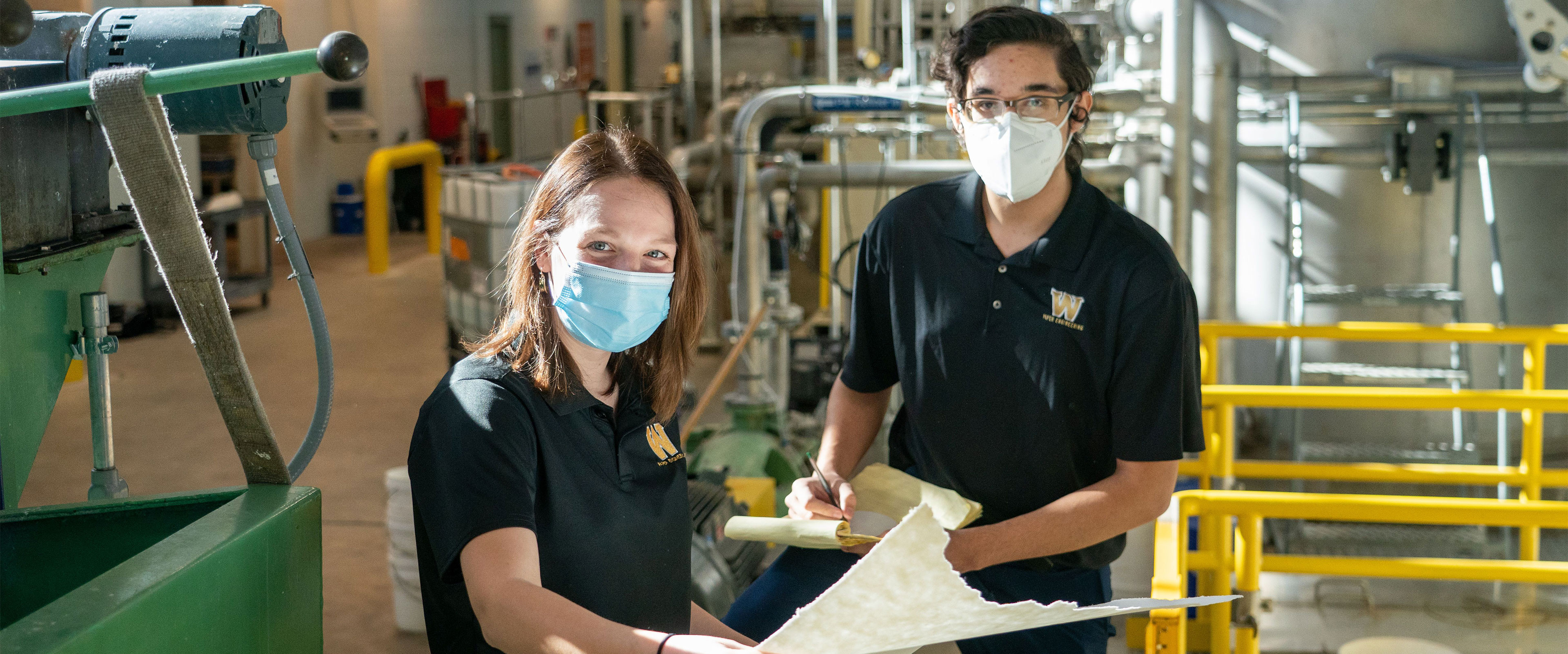 Two paper technology students holding a paper sample off the machine