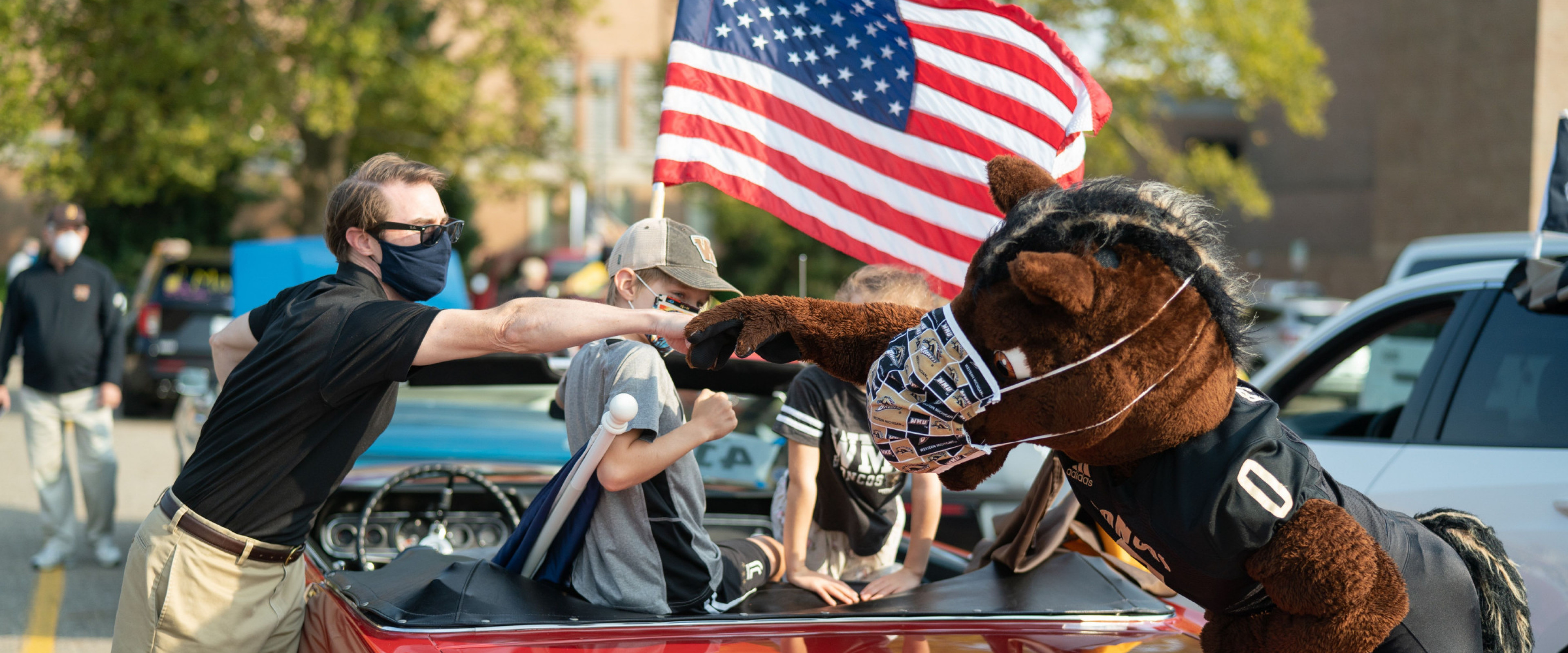 Buster Bronco bumps the fist of a man during the parade.
