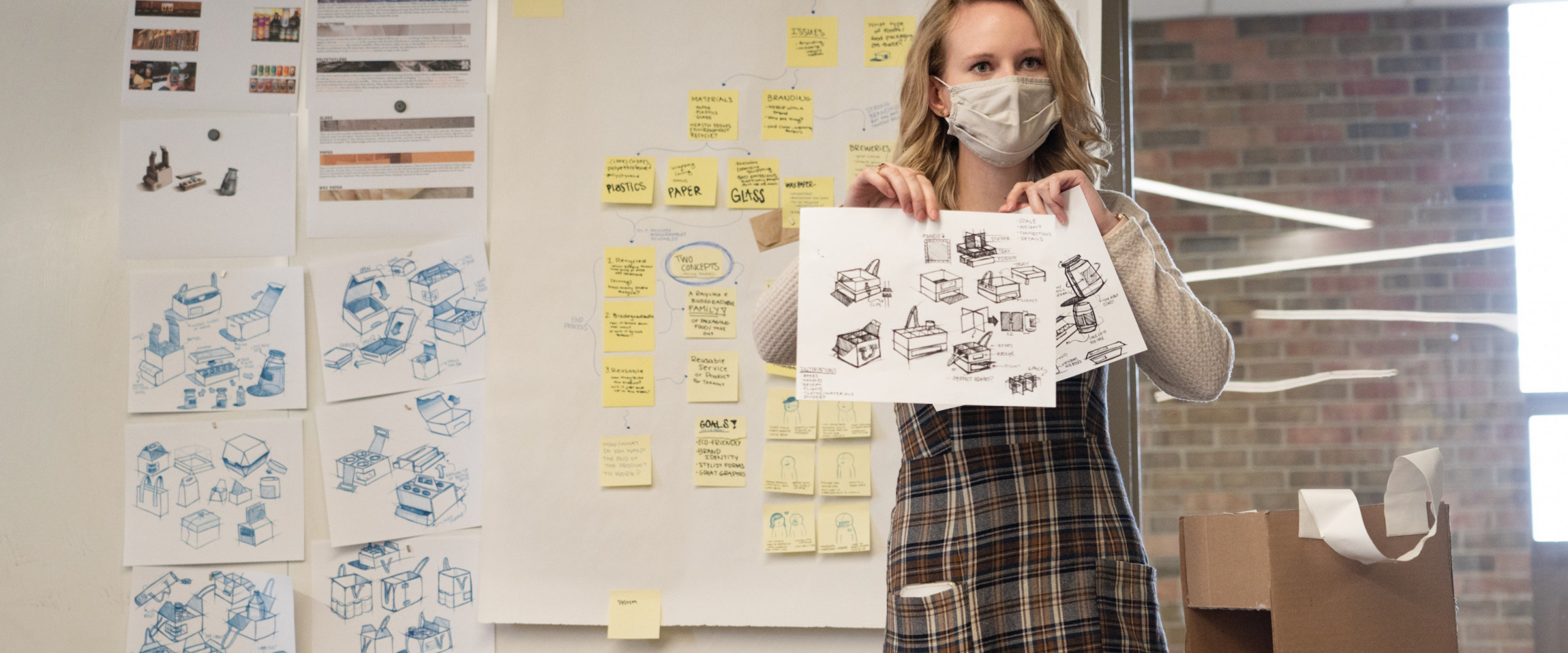 A product design student presents sketches to her class.