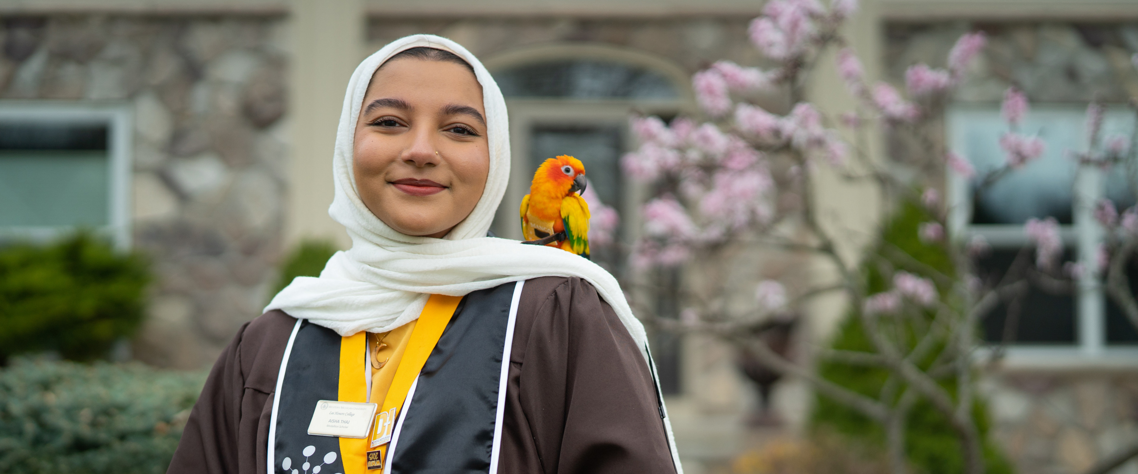 Aisha Thaj poses for a photo with her pet parrot on her shoulder.